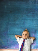 Little schoolboy with blackboard in background — Stock Photo