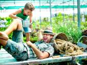 Young boy playing with his father in a green house — Stock Photo