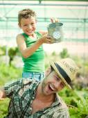 Happy Young boy playing with his father in a green house — Stock Photo