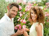 Boy gives his woman a flower in a greenhouse — Stock Photo