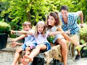 Family having fun with a barrow in a greenhouse — Stock Photo