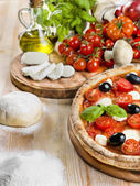 Composition of Italian pizza with tomato, mozzarella, basil and olives — Stock Photo