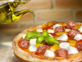 Italian pizza with tomato, mozzarella, peppers salami and basil — Stock Photo