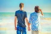 Young Couple Walking at the Beach While Holding Hands — Stock Photo