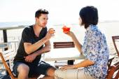 Happy couple drinking a spritz by the sea — Stock Photo