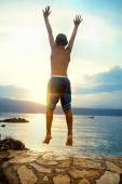 Boy jumping and taking a deep breath at the sunset — Stock Photo