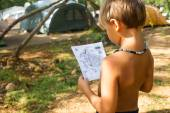 Young boy looking on the map his tent on the camping — ストック写真