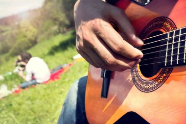 Group of happy friends with guitar having fun outdoor