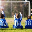 Young boys in uniform watching their team while playing football — Stock Photo #72666553