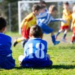 Young boys in uniform watching their team while playing football — Stock Photo #72666697