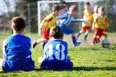 Young boys in uniform watching their team while playing football — Stock Photo