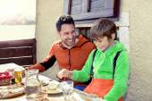 Father and son having lunch in a chalet in the mountain — Stock Photo
