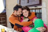 Couple hug each other and eat something at the ski resort — Stock Photo