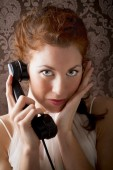 Beautiful woman is phoning with a vintage phone — Stock Photo