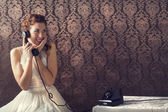 Beautiful young woman on the phone in livingroom in her English — Stock Photo