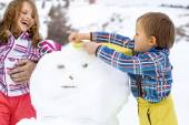 Brother and sister  building a snowman — Stock Photo