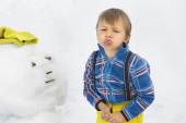 Little angry boy and a snowman — Stock Photo