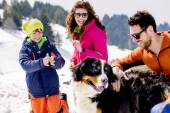 Family with dog having fun in the snow — Stock Photo