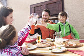 Family cheers in a mountain chalet — Stock Photo