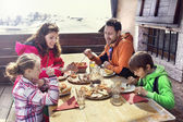 Family having lunch in a chalet in mountain — Stok fotoğraf