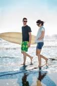 Couple of surfers running on the seashore — Stock Photo