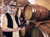 Wine producer showing his bottle of wine in front of the barriques — Stock Photo