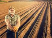 Farmer in front of his cultivated field — Stock Photo