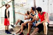 Basketball players take a break sitting on a low wall — Stock Photo