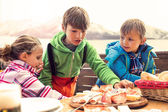 Sons have lunch in chalet in the mountain — Stock Photo
