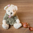 Toy teddy bear and tea kettle and cup on wooden background — Stock Photo #64034135