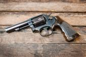 Black revolver gun with bullets isolated on wooden background — Stock Photo