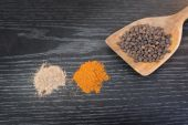 Assorted spices and condiments on table black wooden — Stock Photo