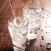 Drinking water is poured into a glass — Stock Photo