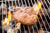 Grilled pork chop on the flaming grill — Stock Photo