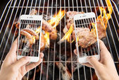 Friends using smartphones to take photos of sausage and pork cho — Stock Photo