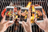 Friends using smartphones to take photos of sausage and pork — Stock Photo