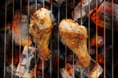 Chicken legs grilling over flames on a barbecue. — Stock Photo