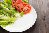 Empty plate with tomatoes and vegetable waiting for food. — Stock Photo