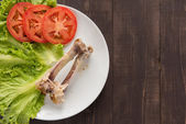 Bone chicken and vegetable on wooden background. — Stock Photo