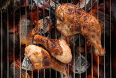 Grilled chicken thigh over flames on a barbecue — Stock Photo