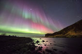 A beautiful green and red aurora dancing over the,skogafoss — Stock Photo