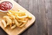 French fries with ketchup on wooden background. — Stock Photo
