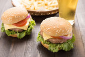 Bbq hamburger with french fries and beer on the wooden backgroun — Stock Photo