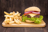 Cheeseburgers with french fries on wooden background — Stock Photo