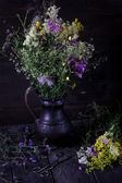 Jug with flowers from a medow on dark wooden table. Style rustic, — Stock Photo