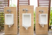 White urinals with ceramic tile on wall. — Stock Photo