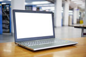 Laptop with blank screen on the table in library — Stock Photo
