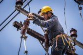Electrician working on the electricity pole — Stock Photo
