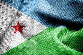 Djibouti flag on fabric surface — Stock Photo