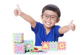 Cute boy playing with letters and showing thumb up sign. — Stock Photo
